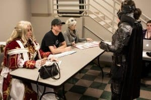 Adjudicating cosplay. Salt Lake Comic Con cosplay technical judges Melissa Spencer, Aaron Forrester and Tia Dworshak, with administrative help from Lynsey Marie Mitchell. Technical Cosplay Adjudicators, hard at work and taking their job very seriously. Photo, courtesy of Robert Hirschi