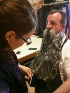 Alea, trimming beard and applying crepe hair to performer's face for Thror